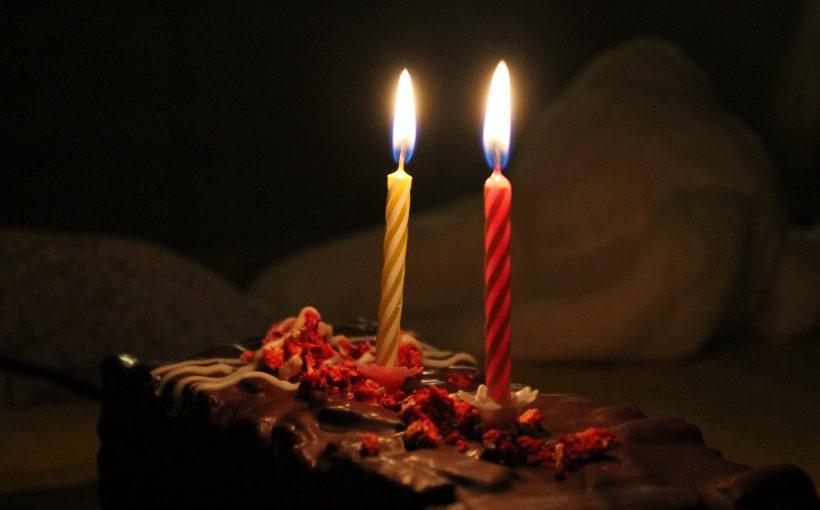 close-up van een taart met twee kaarsjes erop, in een donkere ruimte