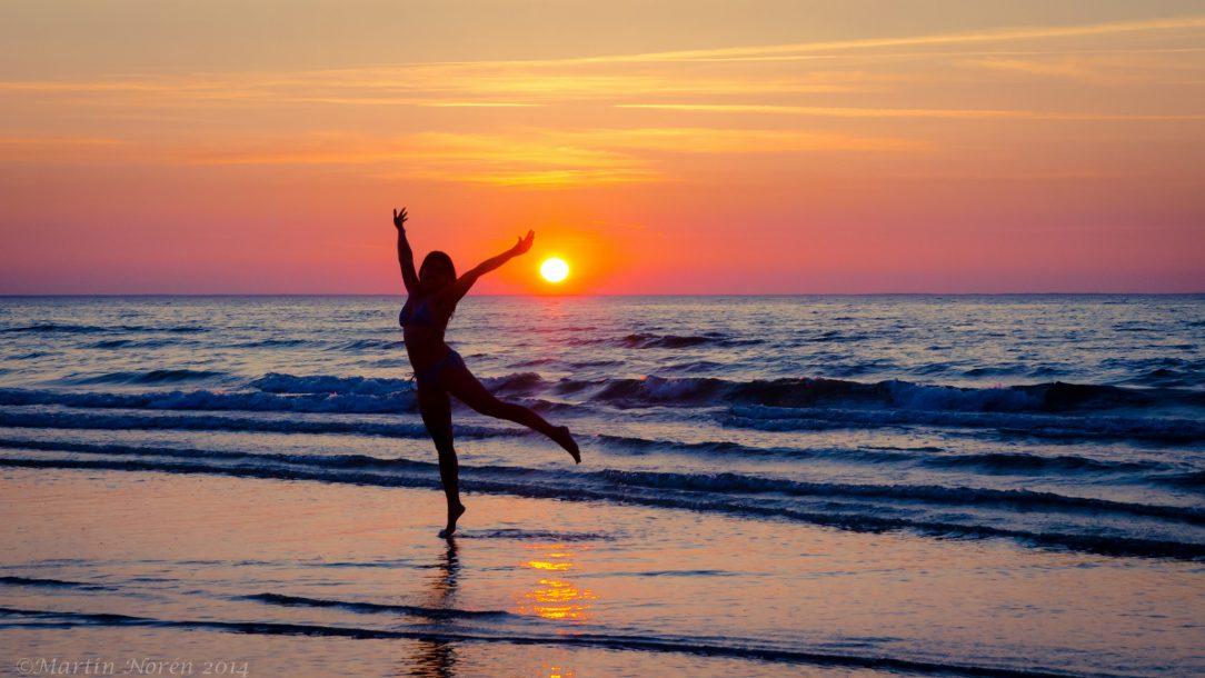 Een vrouw danst alleen op het strand, bij een ondergaande zon. Misschien is ze vrijgezel, misschien ook niet... Het ziet er hoe dan ook vrolijk uit.