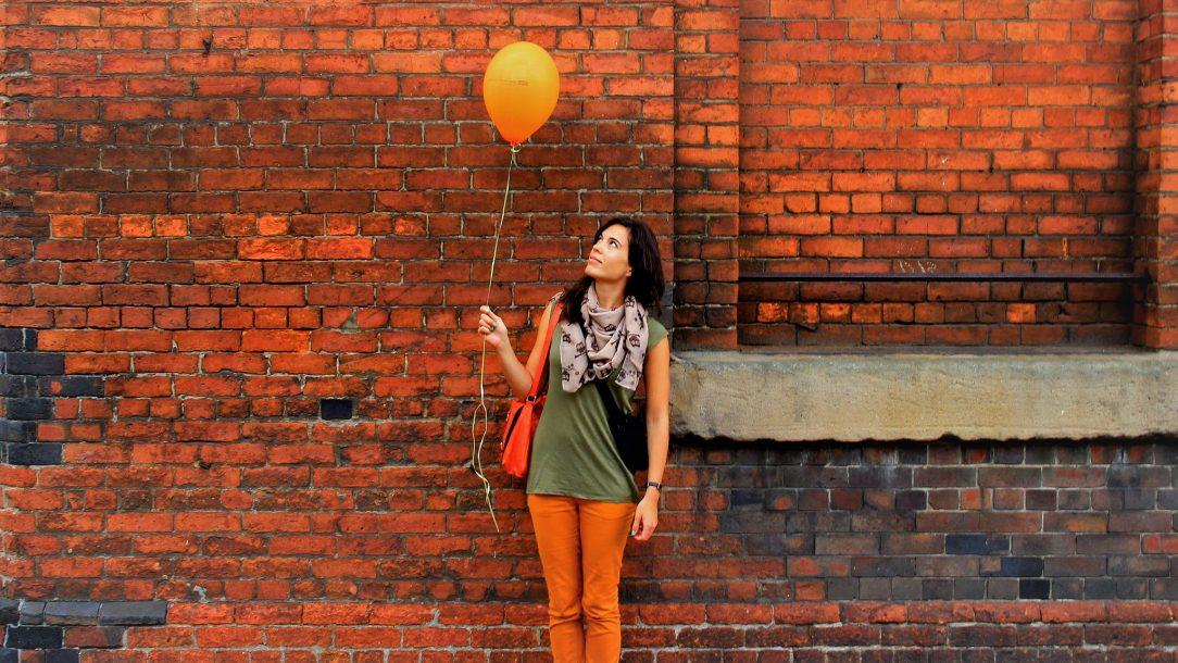 Een jonge vrouw staat voor een muur en kijkt naar een ballon, die ze aan een touwtje vast heeft. Ze ziet er verlegen en rustig uit; niet als een durfal.