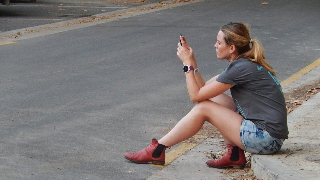 Een jonge vrouw zit op de stoep en kijkt naar haar smartphone.