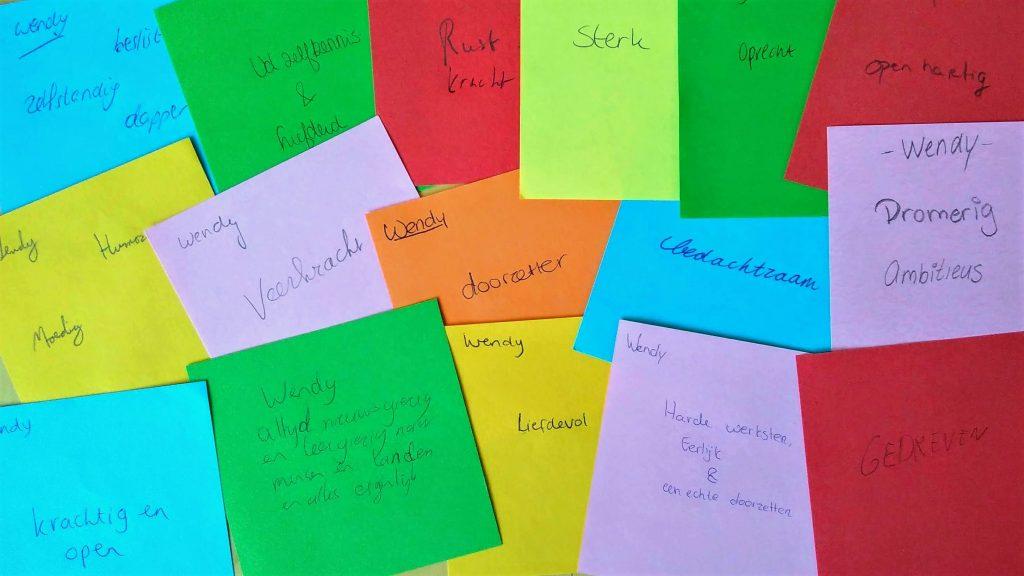 """Allerlei kleuren post-itjes waarop medetrainees antwoord geven op de vraag """"Hoe kom ik over op anderen?""""."""