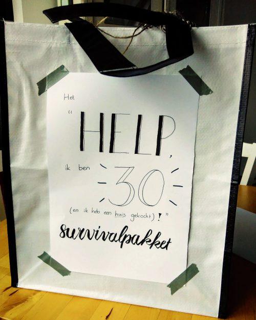 """een tas met daarop de tekst """"Het """"Help, ik ben 30 (en ik heb een huis gekocht)!"""" survivalpakket"""""""