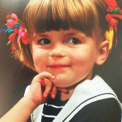 Een foto van mijzelf als klein meisje, gemaakt door een fotograaf. Ik heb een matrozenpakje aan en balonnetjes in mijn haar.