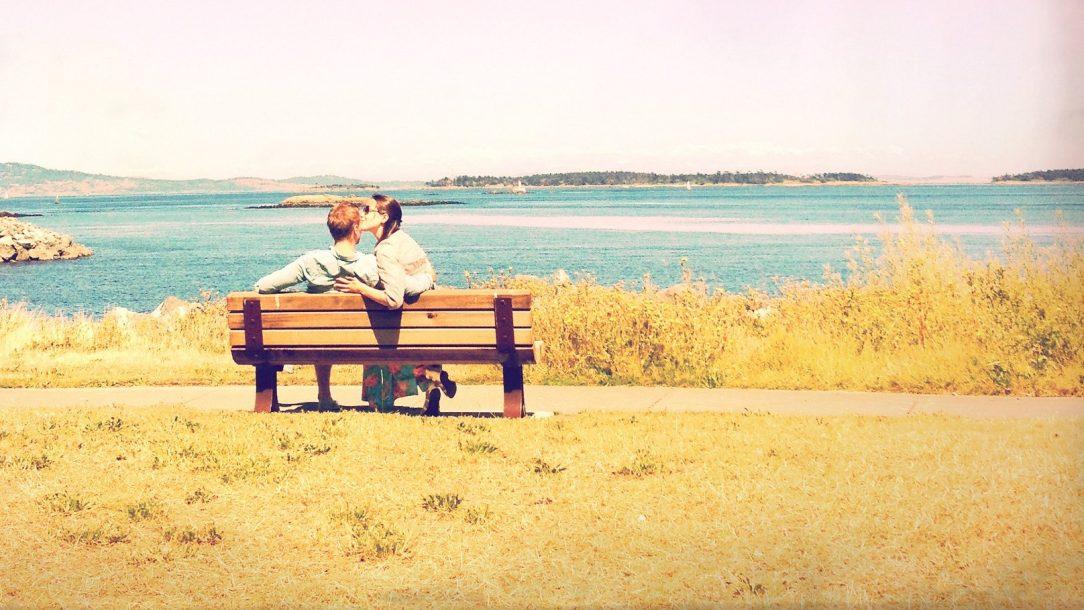 een verliefd stel zit op een bankje aan het water