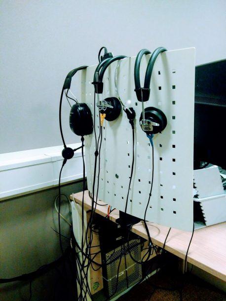 een scherm waar meerdere koptelefoons overheen hangen
