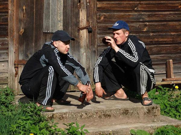 twee mannen doen de slav squat in adidas outfit
