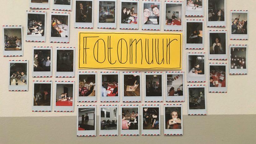 """een stuk papier met daarop de tekst """"Fotomuur"""", daaromheen allerlei polaroid foto's van het weekend in Den Haag"""