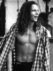 zwart-wit foto van Eddie Vedder op het podium, met ontbloot bovenlijf (oelala), ongeveer 25 jaar geleden