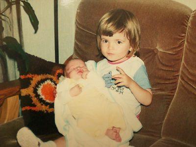 Ik - twee jaar oud - zit op een bank, met mijn kersverse broertje op schoot.
