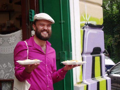 de gids komt naar buiten met twee borden vol pierogi, tijdens de Polish Food Tour in Krakau