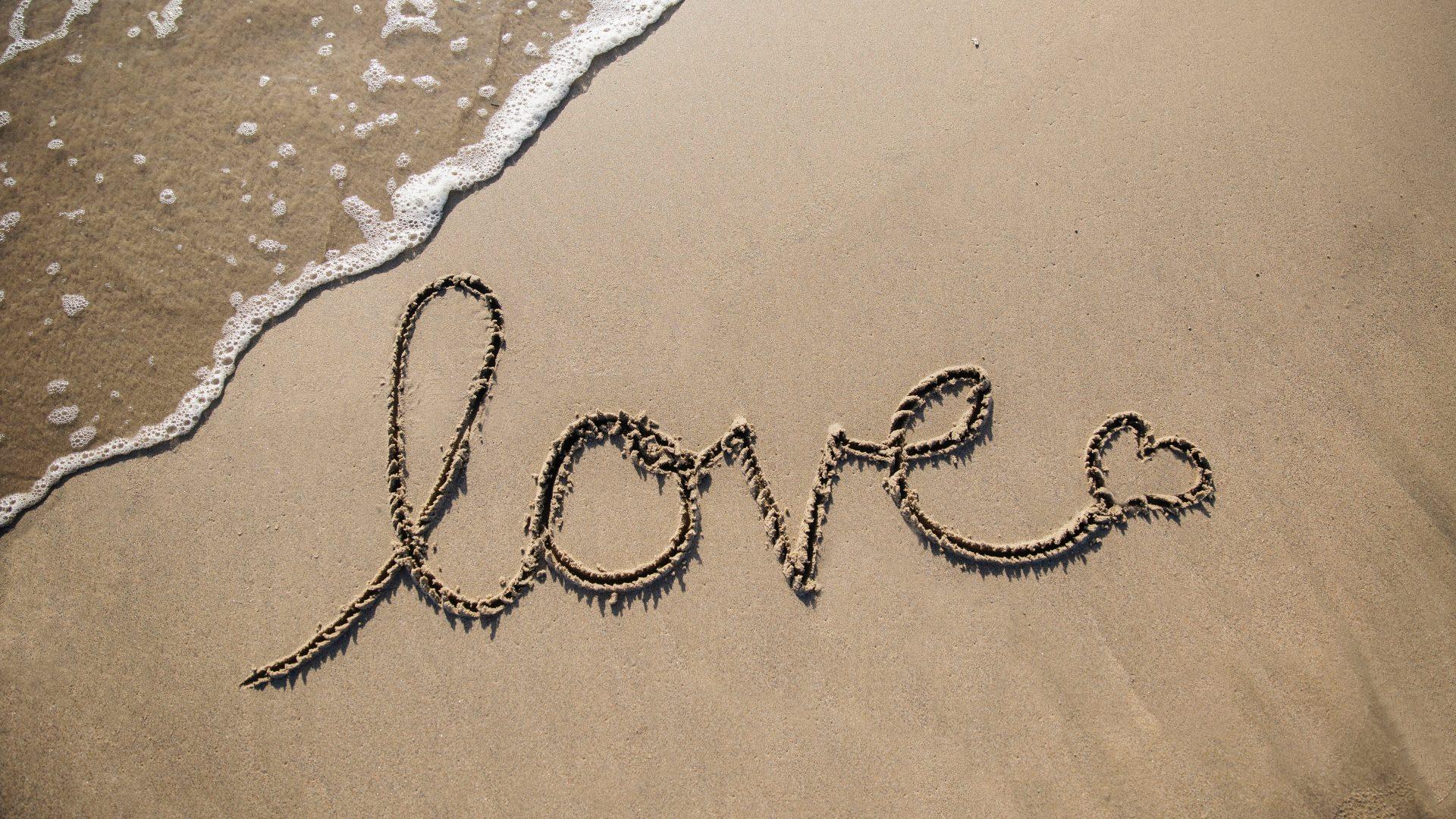 Het woord 'love' staat op het strand geschreven. Zeewater spoelt het bijna weg.