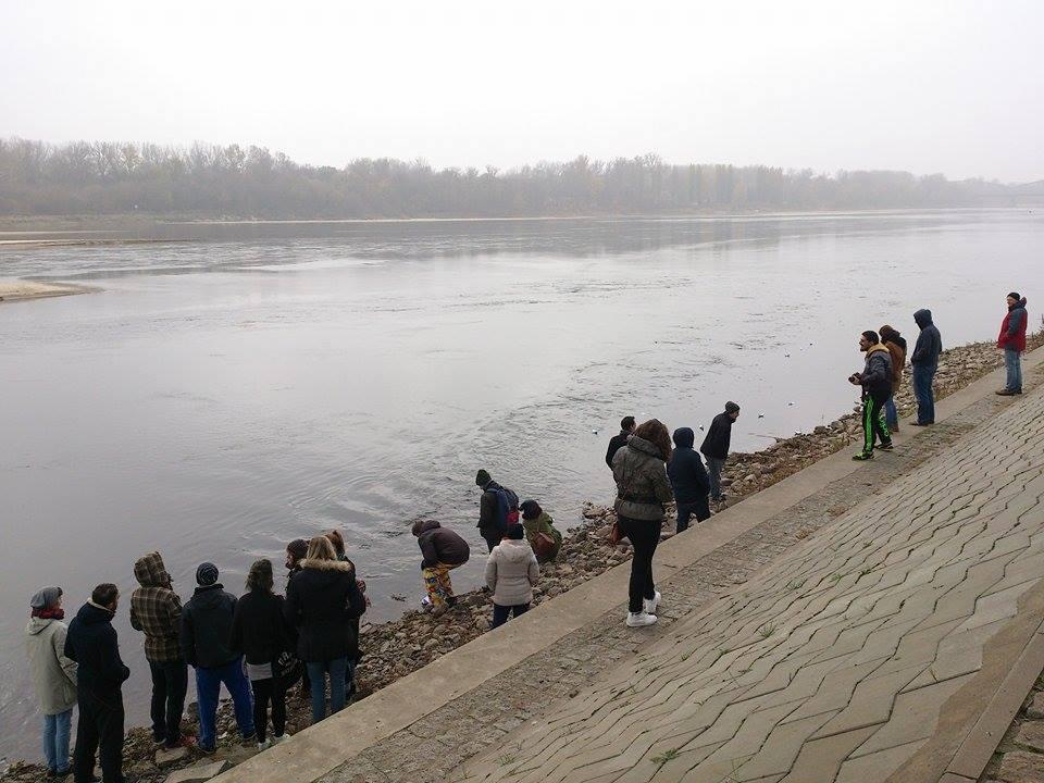 een groep jongeren laat de door hen gevouwen bootjes meevoeren door de rivier