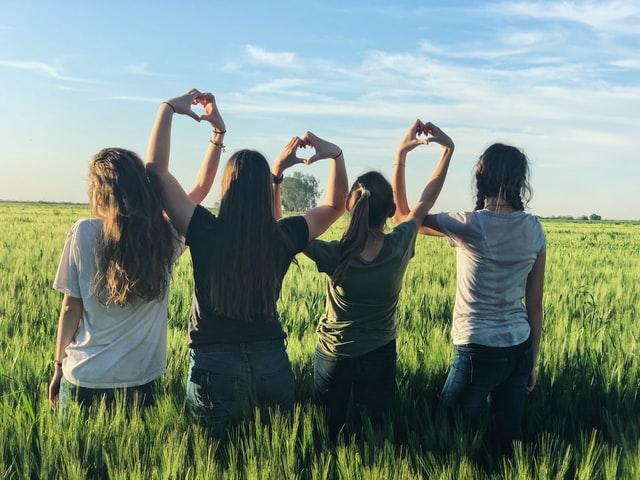vier vrouwen staan naast elkaar in een grasveld en maken samen hartjes met hun handen