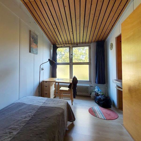 een kamer in de Lioba School voor Vrede, met een eenpersoonsbed, een tafeltje en een stoel, een wastafel en een kledingkast